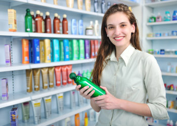 young lady standing in beauty products stall in drugstore