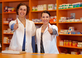 Two happy pharmacists in pharmacy holding their thumbs up