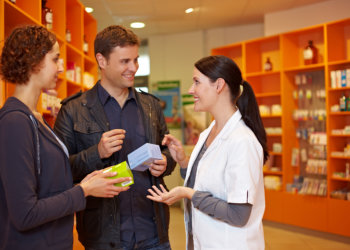 Happy pharmacist talking to a couple in a pharmacy